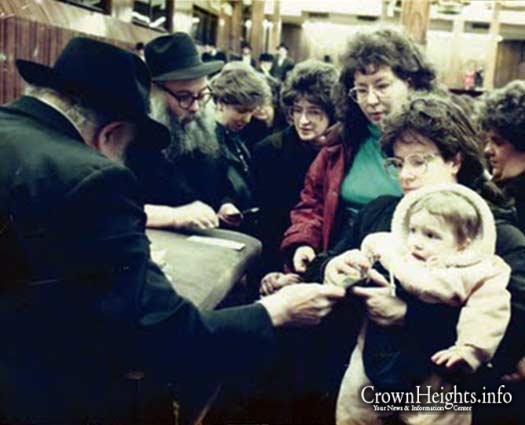 Mrs. Pesha Leah Lapine (holding her child) receiving a dollar from the Rebbe.