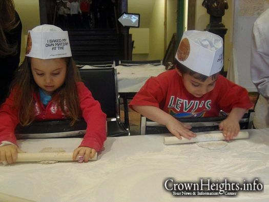Jayden and Joshual roll out their matzah dough at the Living Legacy Matzah Bakery.
