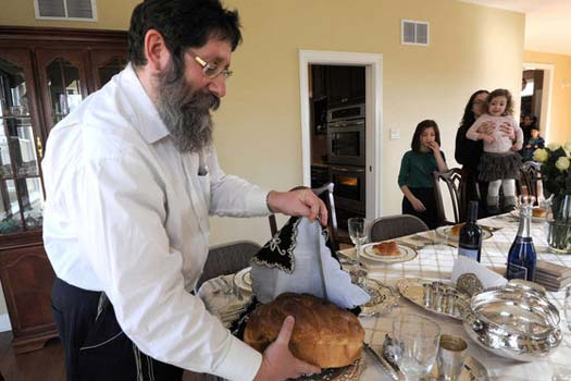 Rabbi Mendel Mangel puts the challah for Shabbat dinner on the table in his Cherry Hill home.