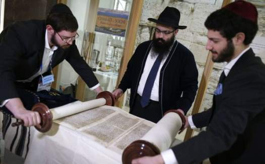 Sochi Rabbi Ari Edelkopf (C), Rabbi JJ Hecht (R) and Rabbi Dovid Katz unroll a Torah scroll in one of several prayer centres set up to cater to Jewish visitors to the Sochi Games.