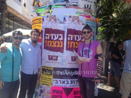 "Lubavitchers put on Tefilin with Israelis in Tel Aviv. Behind them are banners proclaiming ""With G‑d's help, we will prevail."" Photo: Shturem.net."