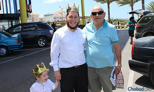 Purim came to the islands in royal form: Rabbi Blasberg and his son deliver mishloach manot gifts of holiday treats.