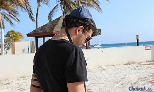 At a Lag BaOmer barbecue on the beach, Jon Atias performs the mitzvah of wrapping tefillin.