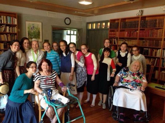 Girls from Europe visiting with the elderly at a senior citizen center in Gothenburg, Sweden.