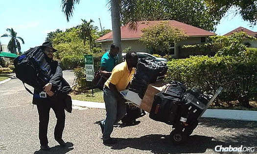 The rabbi brings a Torah to Jamaica, carrying it to the new Chabad center.