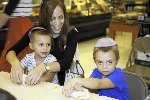 "Miriam Rechtshafer, of Coral Springs, with sons Eli, 3, and Avrami, 4, roll dough for challah bread at the ""Challahpalooza Family Fest,"" co-hosted by the Chabad of Tamarac and the Tamarac Winn-Dixie."