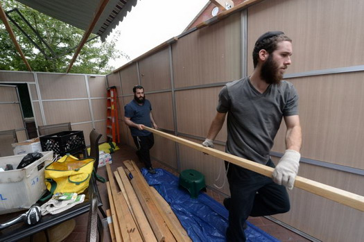 Zalmy Chesney, right, (grey shirt), and his brother Bentzy, of Crown Heights, build a sukkah on the second floor deck of a Borough Park synagogue. Photo: Todd Maisel/NY Daily News.
