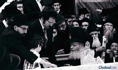 """Circa 1975: Stuart Nelkin and his son, Jay, join Rabbi Shimon Lazaroff, left, of Chabad Lubavitch Center Regional Headquarters in Houston in presenting the key of the Chabad House in Austin, Texas, to the Rebbe. Lazaroff's advice to young shluchim mirrors the Rebbe's words: """"Be totally dedicated ... and the children will look at you, and see what you do and how you behave, and this will rub off on them."""" (Photo: Chabad of Texas Archives)"""