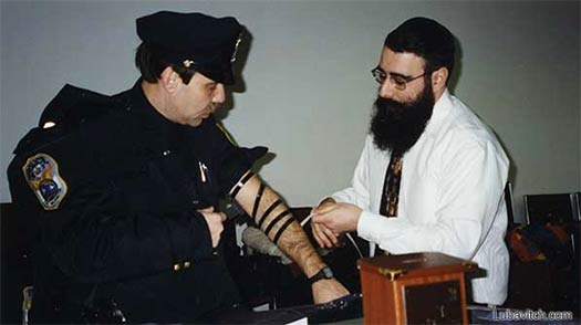 Rabbi Shalom Paltiel assists an officer with the putting on of Tefillin (Photo: Lubavitch Archives).
