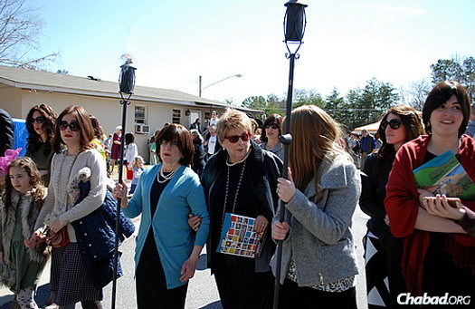 Women march in the procession holding torches. Rashi's mother, Sara Lieberman, in the blue sweater, spoke at the event, describing some of the many ways she interacted and learned from her daughter.