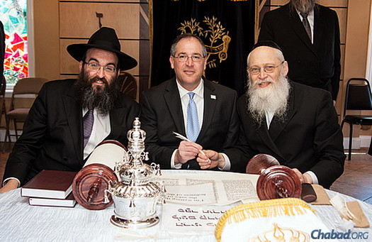 Rabbi Hirshy Minkowicz, left, joins Mike Bodker, the Jewish mayor of Johns Creek, Ga., and scribe Rabbi Moshe Klein in writing a letter in the Torah scroll dedicated to Rashi.