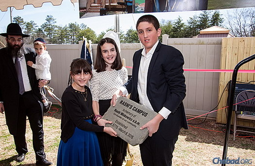 """Tonia, Henya and Yoel Minkowicz lay the cornerstone of the new facility, """"Rashi's Campus."""" At the far left is Rabbi Minkowicz, holding the family's youngest child, Alter."""