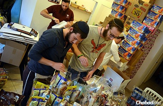 "Packing up food gifts to be sent to ""lone soldiers"" in the Israeli Defense Forces, as part of this year's Purim project run by the Chayal el Chayal (""Soldier to Soldier"") organization."