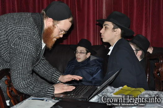 Rabbi Mendy Mochkin, JEM's lead interviewer, scanning letters while Manchester Yeshiva students look on.