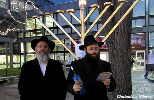Rabbi Shmuel Posner, left, director of the Chabad House of Greater Boston, with Abrams lighting a public menorah during Chanukah 2011.