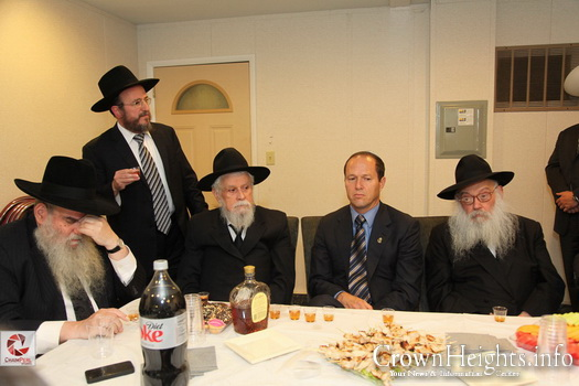 Rabbi Binyomin Klein sitting to the right of then Jerusalem Mayor Nir Barkat at a Farbrengen at the Ohel.
