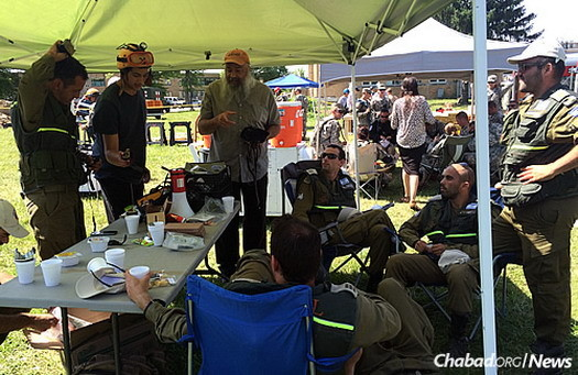 Tefillin in hand, the rabbi chats with the visiting Israelis in the U.S. Midwest.