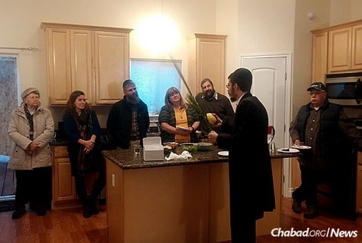 Rabbi Mendy Greenberg helps community members in Wasilla, Alaska, shake the lulav and the etrog over the Sukkot holiday in his home and new Chabad House that he co-directs with his wife, Chaya.