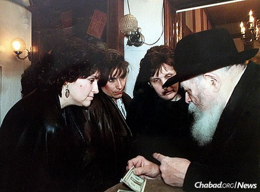 The editorial committee of the cookbook, from left, Cherna Light, Cyrel Deitsch and Esther Blau, receive dollars and a blessing from the Lubavitcher Rebbe—Rabbi Menachem M. Schneerson, of righteous memory—for their work.