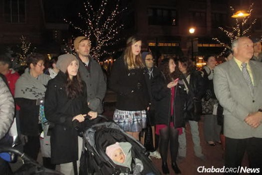 Young families, like those here at this year's public menorah lighting, are drawn to the many new Jewish programs in town for grownups and kids alike.
