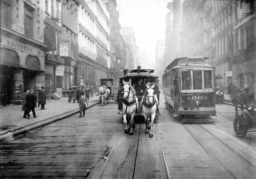 A New York City trolley shares the street with a horse and buggy in 1917.