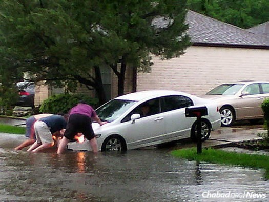 Community members help a neighbor push his flooded car out of the water.