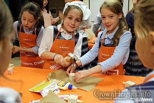 Kids make Chanukah dreidels from wood at a local Home Depot holiday workshop.