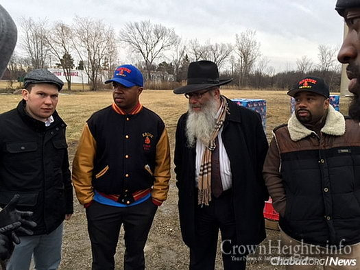"""Rabbi Yisroel Weingarten, director of Chabad House Lubavitch of Eastern Michigan, back in March helping distribute bottled water to residents in need. Now, a free sponge can also aid those still grappling with water issues. With him, from left: Jewish boxer Dmitry Salita, and Detroit boxing trainers Javan """"Sugar"""" Hill and Travone Chambers."""
