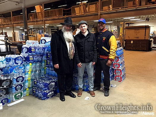 The rabbi, Salita and Hill in a Flint-area warehouse organizing bottled water for delivery.