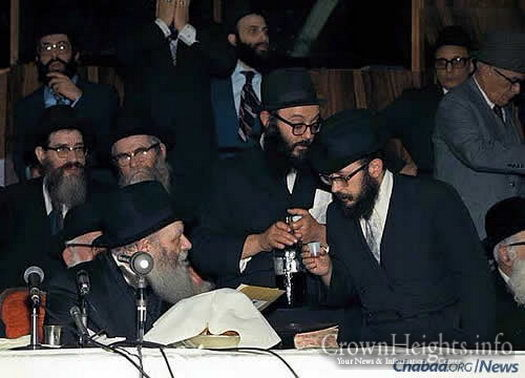 "The rabbi approaches the Rebbe for a private word and a ""l'chaim"" during a farbrengen in the 1970s."