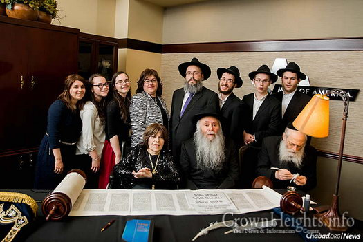 Surrounded by family, Chabad-Lubavitch emissaries in Minnesota Rabbi Asher and Sema Zeilingold, seated at center, celebrated five decades of leadership this year with the writing of a new Torah scroll.