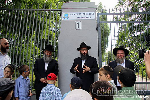 Stambler addresses the crowd. On the far left is Zelig Brez, the community's director, and on the far right is Rabbi Reuven Chupin, director of the yeshivah. Kaminezki looks on.