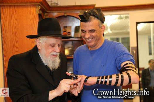 Rabbi Binyomin Klein, OBM, puts on Tefillin with Mr. Moshe Kachlon, Israels then minister of social welfare.