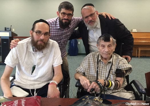 From left: Rabbi Mendel Brikman, Chaim Marcus and Rabbi Shmuel Greenberg help Bill Shank, 90, celebrate his bar mitzvah.