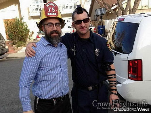 Rabbi Choni Marozov, co-director of Chabad of S. Clarita Valley, wraps tefillin with a Jewish firefighter.