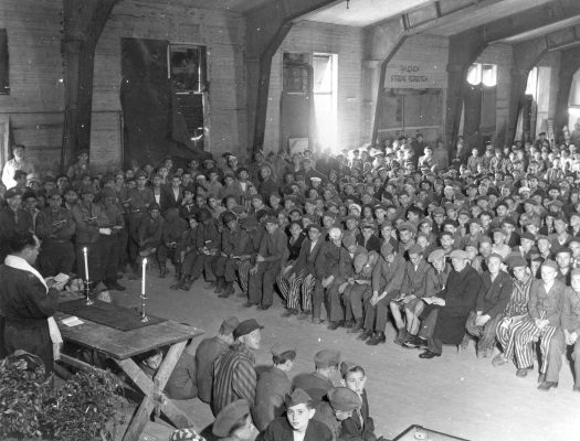 Rabbi Herschel Schacter leading a prayer service for survivors in the liberated Buchenwald camp in Germany in 1945.