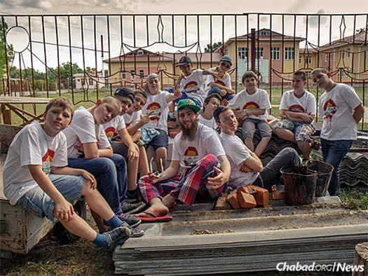 The FJC grounds in Zhitomir house the Alumim orphanage, among other programs. Here, a Yeka boys' bunk posed with the soccer field and the campus's main building behind them. (Photo: Avraham Edery)