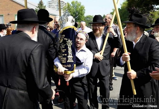 Ariel Melachy, shown here holding the Torah, has become a fixture at the Montreal Jewish Center. He announces page numbers for certain prayers during services, informs congregants of minyan times and makes other special announcements.