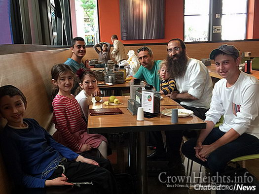 The rabbi, four of his children and students Kian Marghzar, left, across from his father, and Brent Freed, lower right, enjoy a meal at the campus eatery.