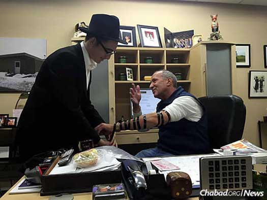Mendel Gopin wraps tefillin with those on his Friday route . . .