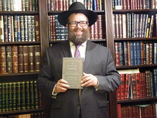 Rabbi Chaim Miller with his newly-published work. Photo: VIN News.