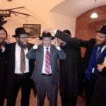 Senator Tries on Chabad Rabbi's Fedora