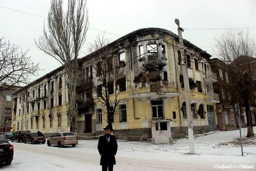 Rabbi Mendel Cohen, chief rabbi and Chabad-Lubavitch emissary in the Ukrainian city of Mariupol, stands in front of the burnt-out shell of the eastern city's central police station.